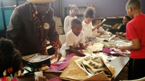 With artists Heidi Barr and Nickki Payne, youth at Healthy Choices afterschool make fabric photo transfers for a garden-based textile art project.